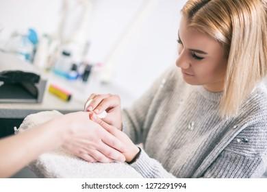 Manicure process at professional saloon. Nail treatment.