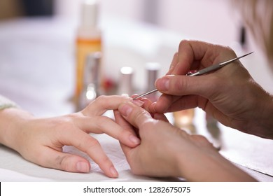 Manicure process. Woman works on younger girl's hands and nails. Close-up.