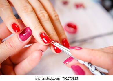 Manicure in progress - Beautiful manicured woman's nails with red nail polish. The industry of beauty and nail care, beauty salons