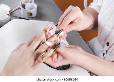 Manicure. Removal of the disposable paper form for escalating of nails