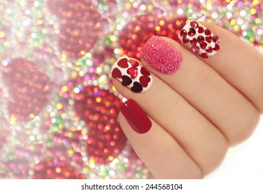 Manicure with rhinestones in the shape of hearts and pink balls on white and red nail Polish on a brilliant background.