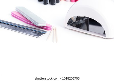 Manicure set for gel nail procedure - Nail LED lamp, colour gel polishes and pink file on white table