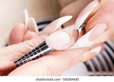 Manicure specialist care by finger nail in beauty salon. Manicurist uses professional manicure tool.  Use of a template (schablon) for acrylic nails