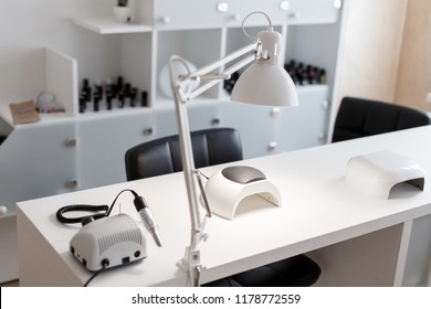 Manicure Studio. White lamp on white table with nail tool