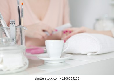 Manicure treatment at nail salon, filing nails, woman hands. Focus on coffee cup and manicure set
