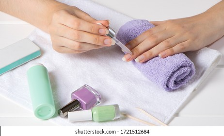 Manicure. A woman applies a moisturizer to the cuticle. Manicure tools, nail polishes, oil. Home nail care, SPA, beauty. Long natural nails. Beauty salon.