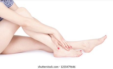 Manicured female long legs and hands with red nails - studio shot - skin care treatment