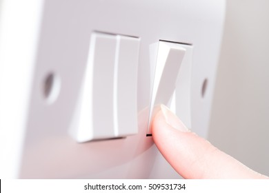 A manicured finger has just switched on a light by pressing a button on a white 4 gang light switch