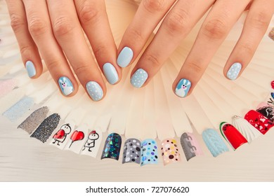 Manicured hands and nail art samples. Woman hands with winter manicure and collection of nail art samples painted in different colors. Female fingers with winter design manicure.