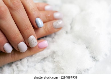 the manicured hands with white blue pink and glitter nails lie on snow
