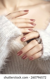 Manicured woman fingernails with natural color nail polish. Manicure and beauty treatment. Warm, soft white sweater and shiny gold rings with brilliants on fingers. Selective focus.