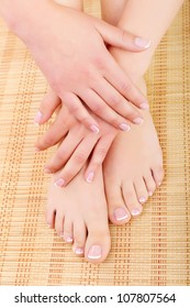 Manicured women's hands crossed on his feet