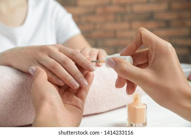 Manicurist applying polish on client's nails at table, closeup. Spa treatment