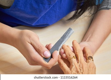 Manicurist filing nails to senior woman. Old woman hands in a nail salon receiving a manicure by a beautician with nail file. Elderly woman is getting a manicure in beauty salon.