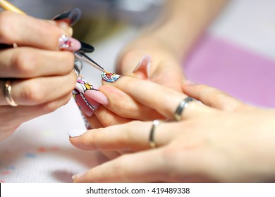 Manicurist master makes manicure on young woman hand