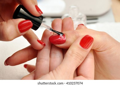 A manicurist paints a customer's nails. Painting nails with red lacquer close-up.