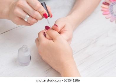 The manicurist paints the nails of women.