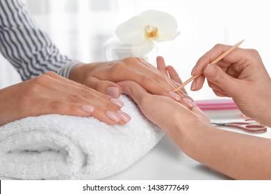 Manicurist preparing client's fingernail cuticles in salon, closeup