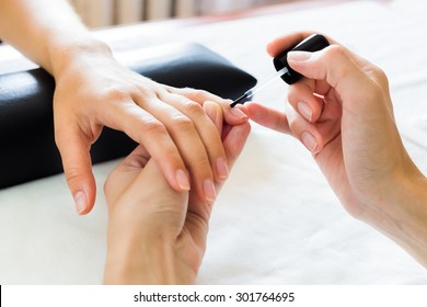 Manicurist putting cuticle softener on the fingernails of a lady client in a beauty salon with a small applicator
