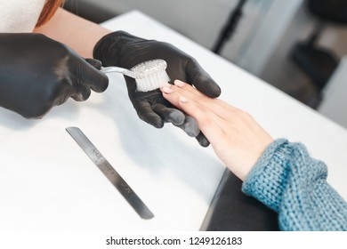 Manicurist removes dust with a brush. The master removed the coating for nail polish from the client.
