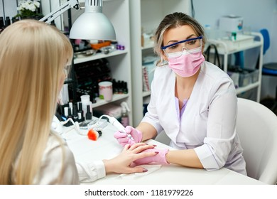 The manicurist removes the old coating on the nails of the blond client inside the beauty salon. The concept of body care.