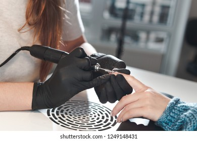 The manicurist removes the old cover from the nail. Beginning of the manicure procedure in the beauty salon.