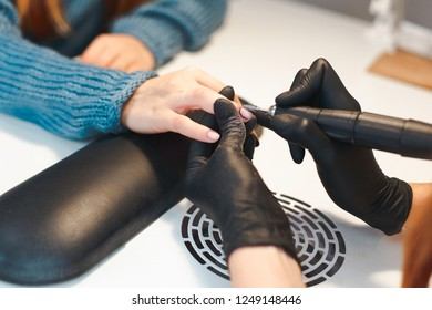 The manicurist removes the old varnish coating from the client's nail. Beginning of the manicure procedure in the beauty salon.