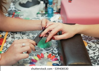 Manicurist woman makes hand fingers manicure for client in the beauty salon. The concept of beauty care for hands.