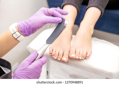 Manicurist work on a woman client feet, make her nails look beautiful. Salon pedicure procedure in process. Professional works in gloves for sterility