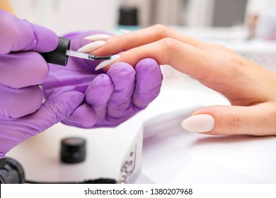 Manicurist work on a woman client hands, make her nails look beautiful. Salon procedure in process. Professional works in gloves for sterility