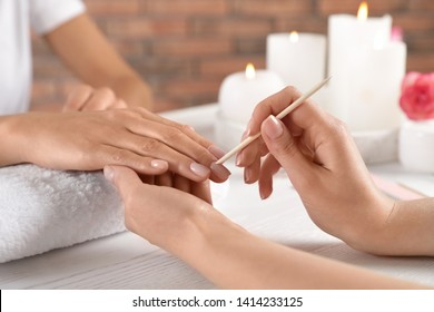 Manicurist working with client's nails at table, closeup. Spa treatment