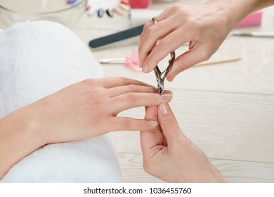 Manicurist working with cuticle nipper. Nail care and cuticle removal at a beauty salon.