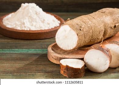 Manihot esculenta (cassava, yuca, manioc, mandioca, Brazilian arrowroot) and tapioca on wooden background. Selective focus