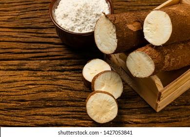 Manihot esculenta. Cassava, yuca, manioc, mandioca, Brazilian arrowroot. Tapioca on wooden background old. Selective focus.