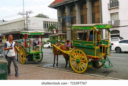 MANILA, PHILIPPINES—AUGUST 2014: The kalesa or horse-drawn carriages are popular rides in the historic Intramuros area in Manila, Philippines