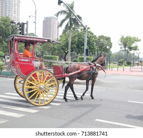 MANILA, PHILIPPINES—AUGUST 2014: A red kalesa or horse-drawn carriage driving around Rizal Park in Manila, Philippines.