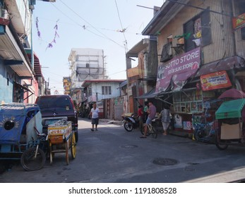 MANILA, PHILIPPINES—MARCH 2018: Wide view showing a side street with people buying from a small roadside store in Pasay City.