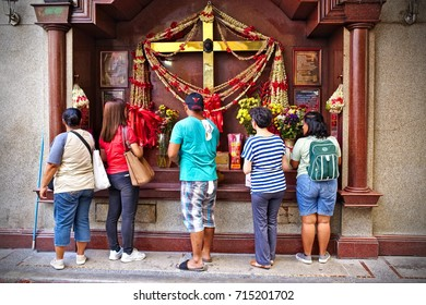 MANILA, April 23, 2016 - A group of Filipinos are worshipping at a street side shrine, showing the combination of oriental tradition with Christianity.