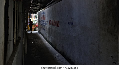 MANILA, April 23, 2016 - A silhouetted boy  is standing at the exit of a dark alleyway in Manila Chinatown.