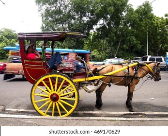 "MANILA CITY, PHILIPPINES - JULY 20, 2016: Drivers park their horse drawn carriages called ""kalesa"" along a street in Manila City waiting for passengers or tourists to ride them."