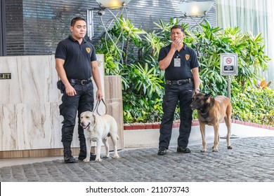 MANILA - FEB 12: Unidentified security guards with dogs at Diamond Hotel on 12 Feb, 14 in Manila. It is estimated 3.7 million of security guards including doormen in the Philippines.