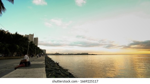 Manila, Metro Manila/Philippines - June 13 2019: A man sits and rests on the sundown Manila breakwater.