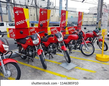 Manila, PH - JUNE 30, 2018: A lot of Jollibee's red delivery service motorbikes that parking in front of Jollibee restaurant, ready to send ordered fast foods to customer's house.