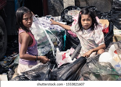 Manila, Philippines - 1/11/2014: Young girls scavenging, recycling trash in the slum. Child labor. Human rights and poverty concept.