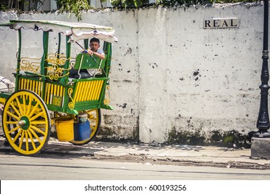 Manila, Philippines - 27 July, 2009: Boy waiting and watching while sitting in the back of a horse drawn carriage in the old colonial district