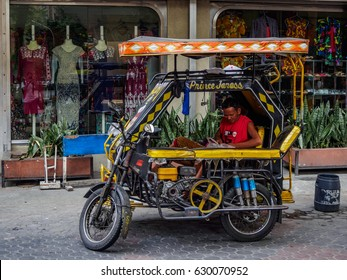 MANILA, PHILIPPINES - APRIL 2nd 2017: A young man sitting in the filipino public transport vehicle motorized tricycle parked by the side of the road on the streets in Manila