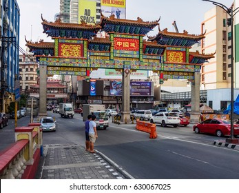 MANILA, PHILIPPINES - APRIL 2nd 2017:Traffic going through the gates of the Chinatown in  Binondo district Manila on a smoggy spring day