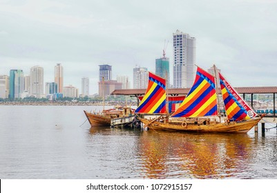 """Manila, Philippines -- April 9, 2018. Illustrative editorial. Example of a traditional Filipino wooden sailing vessel called a balangay. The """"Sultan Sin Sulu"""" is a replica docked in Manila Bay."""