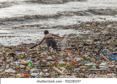 Manila, Philippines - August 23, 2017: A man collects plastic things in a pile of garbage brought by the surf from the sea