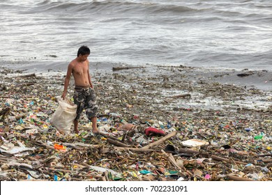 Manila, Philippines - August 23, 2017: A man collecting plastic waste in a pile of garbage in the sea